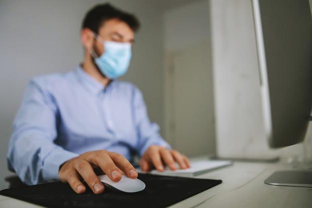 従業員がオフィスに座って、顔にマスクを付け、コロナの発生時にラップトップを使用している