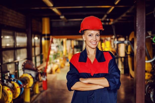 Работник стоит в тэц со скрещенными руками.