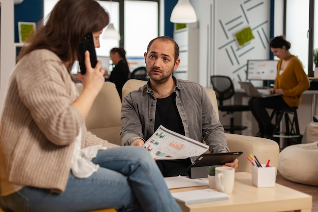 Employee taking at smartphone with business partner sitting on couch looking at documents
