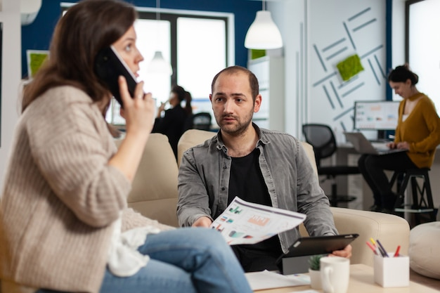 Employee taking at smartphone with business partner