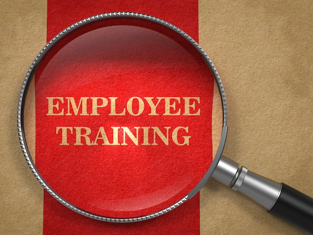 Employee training concept. magnifying glass on old paper with red vertical line background.