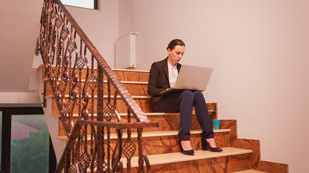 同僚がオフィスの職場を離れる間、金融会社の階段に座って締め切りにラップトップを使用している従業員。現代の金融ビルで働くプロのビジネスマン