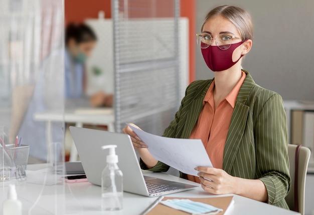 職場でフェイスマスクを着用している従業員