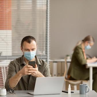 Dipendente che indossa la maschera per il viso in ufficio