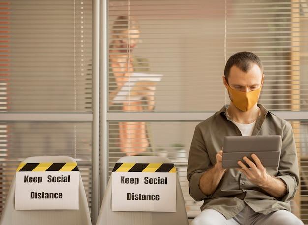 Dipendente che indossa la maschera per il viso prendendo una pausa