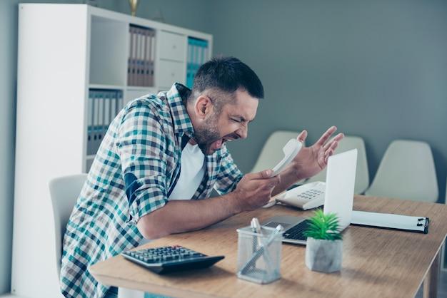 青い市松模様のシャツを着た従業員がオフィスで働いています