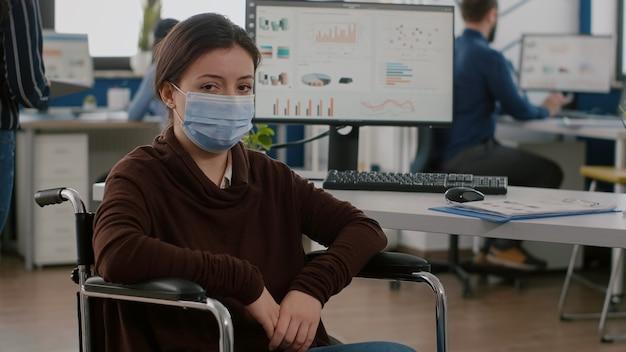 휠체어에 앉아 정면을 바라 보는 코로나 바이러스에 대한 보호 마스크를 착용 한 장애인