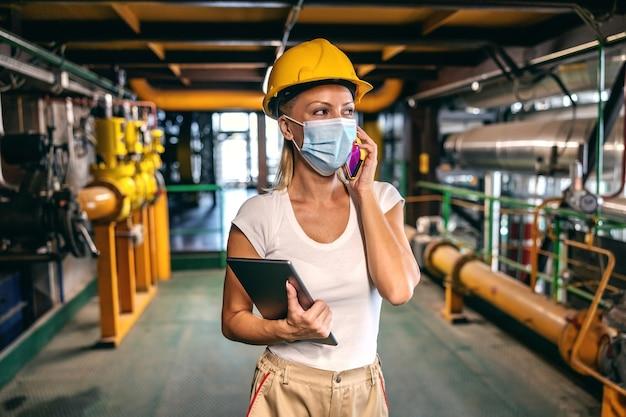 Сотрудник с маской для лица держит планшет в руках и разговаривает по телефону, стоя на заводе