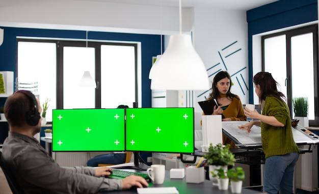 녹색 화면이있는 듀얼 모 니트로 설정을 사용하는 헤드폰을 사용하는 직원, 크로마 키는 비디오 제작 스튜디오에 앉아 분리 된 디스플레이를 모의합니다.