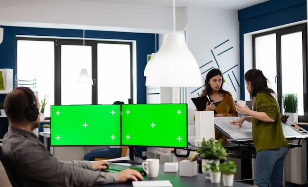 Employee with headphones using dual monitror setup with green screen, chroma key mock up isolated display sitting in video production studio