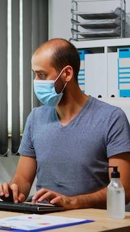 마스크를 쓴 직원은 컴퓨터에서 일하기 전에 사무실에서 항균 젤로 손을 닦습니다. 코로나 바이러스에 대한 소독용 알코올 젤을 사용하여 새로운 일반 사무실 작업장에서 일하는 기업가