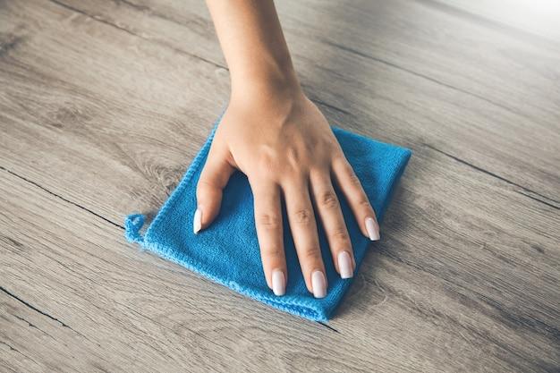 木製のテーブルを拭くマイクロファイバーの布を持つ従業員