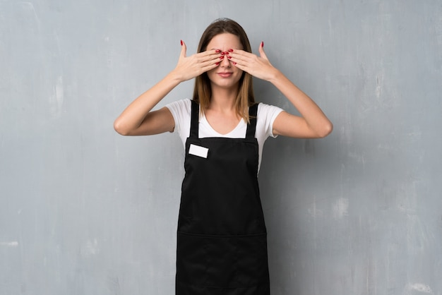 Employee woman covering eyes by hands. surprised to see what is ahead