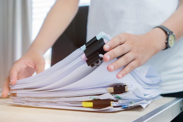 Employee woman hands working in stacks paper files for searching checking unfinished