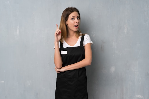 Employee woman thinking an idea pointing the finger up