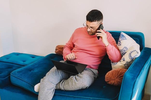 コロナウイルスのパンデミックのため、自宅のソファでノートパソコンを使って作業している従業員