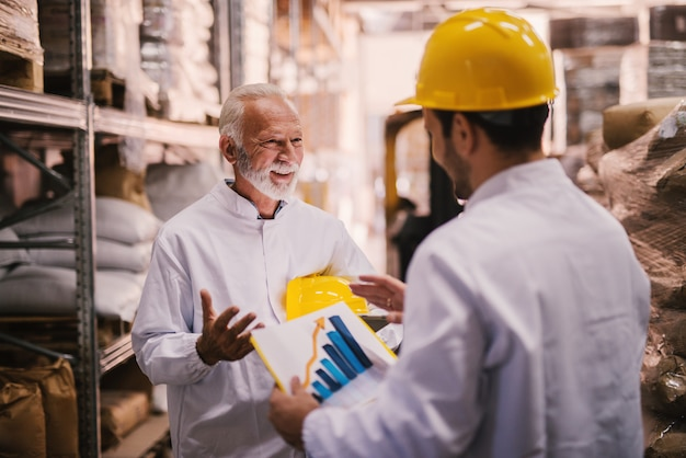 Employees analyzing chart in warehouse.