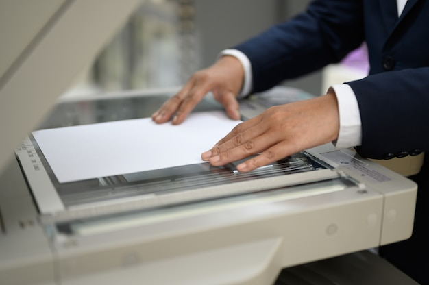 Employees are copying documents with a copy machine at the office.