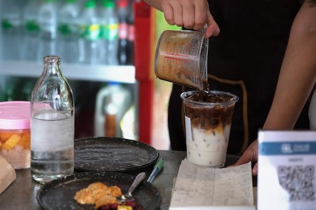 Сотрудники наливают кофе в стаканы, чтобы приготовить латте для клиентов.