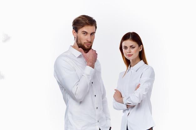 Сотрудники за работой мужчина и женщина в одинаковых рубашках на светлом фоне стоят напротив друг друга.