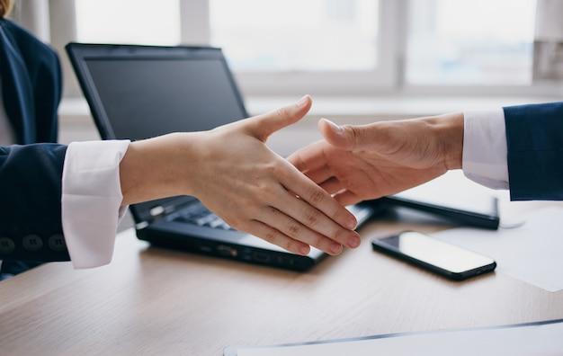 職場の従業員は、テーブルとバックグラウンドでラップトップで握手します。高品質の写真