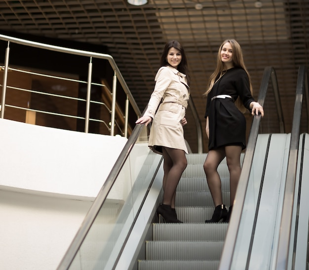 Employees of the company meet the client on the stairs in the foyer of the modern office