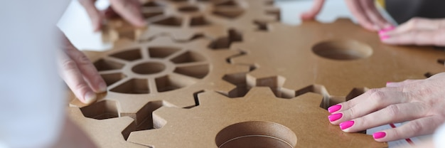 Employees connect together wooden gears on work table