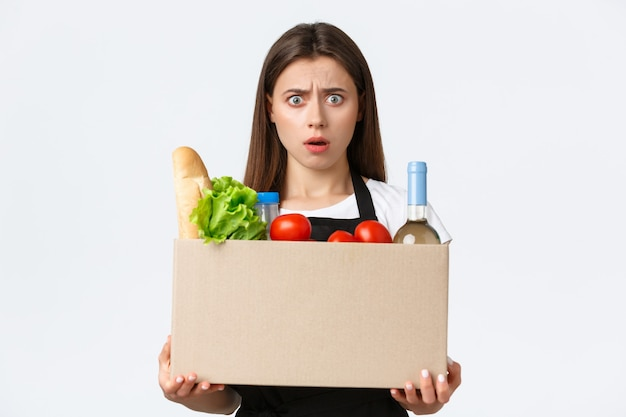 Сотрудники, доставка и онлайн-заказы, концепция продуктовых магазинов. шокированная и сбитая с толку женщина-кассир, продавщица, держащая упаковку товаров, коробку с продуктами и разочарованно хмурясь