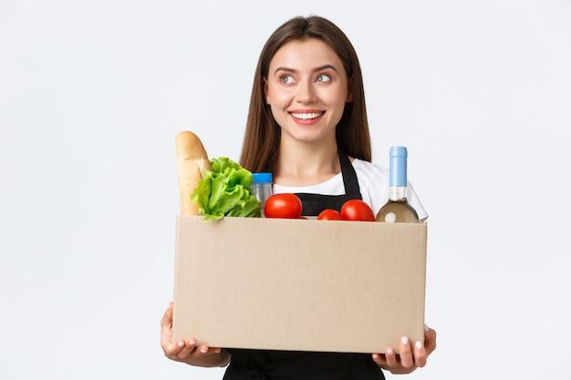 Сотрудники, доставка и онлайн-заказы, концепция продуктовых магазинов. улыбающаяся жизнерадостная женщина-курьер, продавщица упаковала онлайн-заказ в коробку, держит пакет с продуктами и довольна поворотом налево.