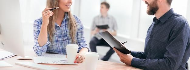 Сотрудники обсуждают деловые документы в офисе