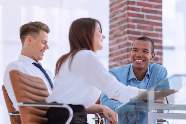 オフィスの職場で新しいアイデアについて話し合う従業員。