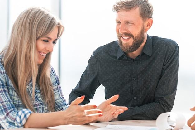 Сотрудники обсуждают рабочие документы, сидя за столом. бизнес-концепция