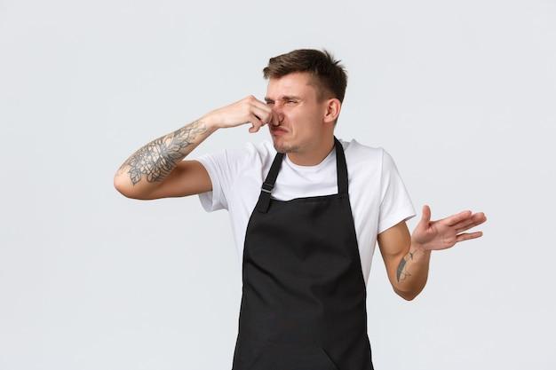 직원, 식료품점 및 커피숍 개념. 짜증나고 지친 재미있는 바리스타, 답답해 보이는 카페, 역겨운 냄새로 코를 막고, 냉장고에서 썩은 것을 어리둥절하고, 흰색 배경