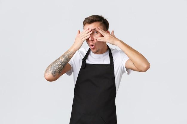 직원, 식료품점 및 커피숍 개념. 흥미로운 바리스타, 검은 앞치마를 입은 남자 웨이터, 무슨 일이 일어나고 있는지 손가락으로 엿보기, 흰색 배경에 서 있는