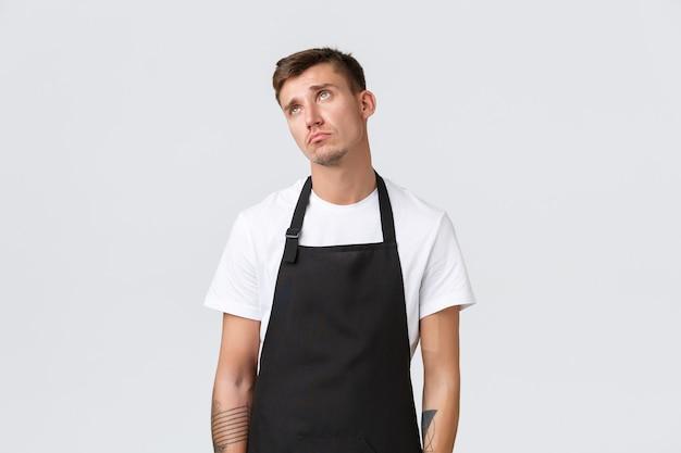 직원, 식료품점 및 커피숍 개념. 마지못해 변덕스러운 바리스타, 웨이터 소원이 바뀌고 왼쪽 상단 모서리가 괴로워하고 슬퍼보이고 서 있는 흰색 배경