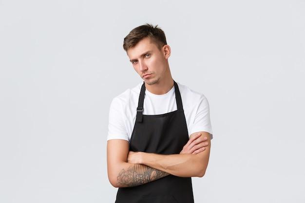 직원, 식료품점 및 커피숍 개념. 심각하고 실망스러운 바리스타, 검은 앞치마를 입은 카페 직원이 카메라를 보고 비판적이고 화난 흰색 배경