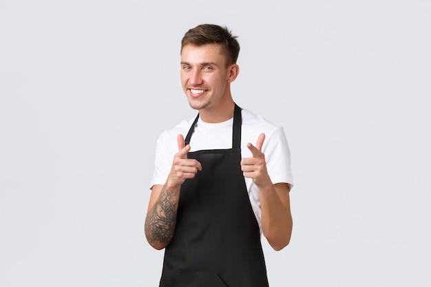Dipendenti, negozi di alimentari e concetto di caffetteria. cameriere biondo bello sfacciato, barista in grembiule nero che sorride ampiamente e punta il dito verso la telecamera, invita gli ospiti, accoglie i clienti.