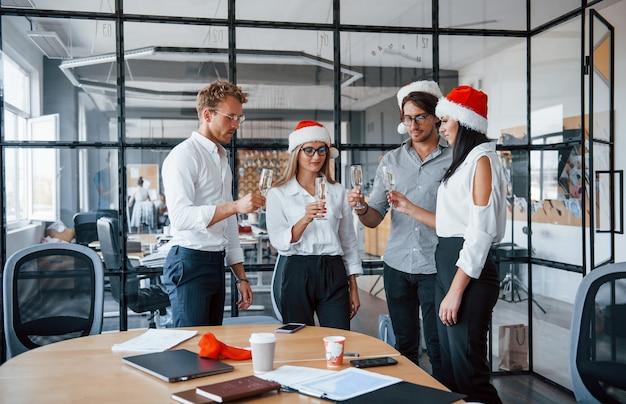 Сотрудники в формальной одежде, бокалах с шампанским и в рождественских шляпах празднуют новый год в офисе.