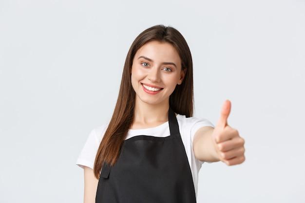 직원, 직업 고용, 중소기업 및 커피숍 개념. 검은 앞치마를 입은 매력적인 미소의 친절한 바리스타가 엄지손가락을 치켜세워 손을 내밀고 모두가 마을에서 최고의 음료를 마시도록 초대합니다.