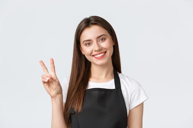 Сотрудники, трудоустройство, малый бизнес и концепция кафе. крупный план дружелюбно выглядящей улыбающейся женщины-бариста, работника кафе в черном фартуке, приветствующего гостей и показывающего знак мира.