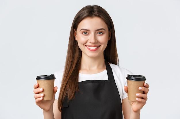 Сотрудники, трудоустройство, малый бизнес и концепция кафе. крупный план улыбающейся дружелюбной женщины-бариста, сотрудницы кафе, обслуживающей две чашки кофе для клиента.