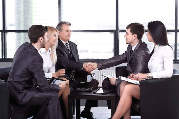Employees look at the handshake of business partners