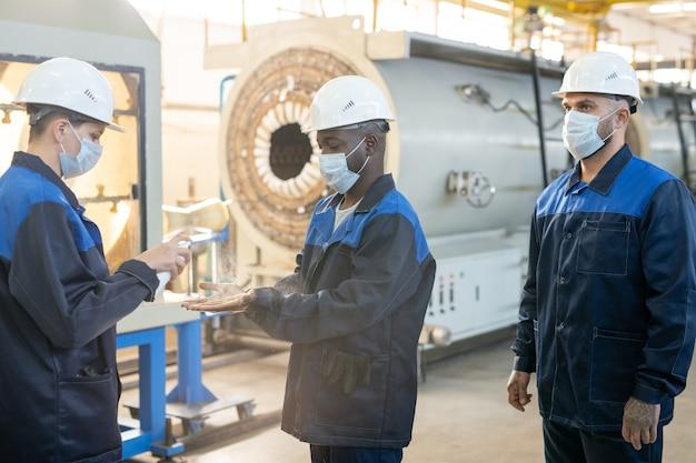 Сотрудники промышленного предприятия стоят у воздушных резервуаров и обсуждают количество товаров на складе
