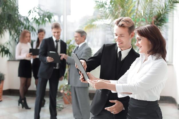 Сотрудники компании с буферами обмена, стоя в офисе