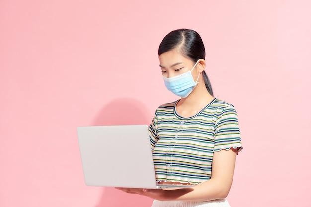 보호용 의료 마스크를 쓴 직원, 사무직 여성이 노트북, 전염병, 코로나바이러스를 들고 있습니다.