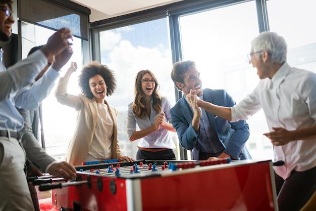 Сотрудники играют в настольный футбол в помещении в офисе во время перерыва, чтобы снять стресс на работе