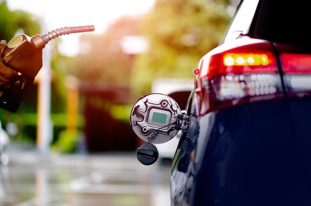 직원들이 차에 연료를 보급할 준비를 하고 있습니다. 운송 및 산업 개념. 차를 채우십시오. 급유 밸브를 급유 넥에 삽입하십시오.