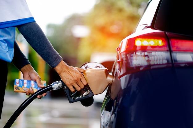 従業員は車に燃料を補給する準備をします。輸送と産業の概念。車をいっぱいにします。給油バルブを給油ネックに挿入します。