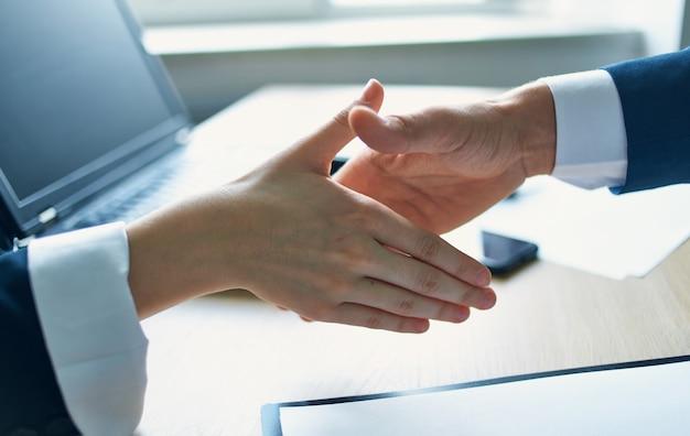 Сотрудники, пожимая руки на работе в ноутбуке документа офисного соглашения.