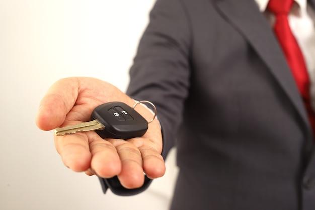 従業員は、車を受け取りに来る顧客に車の鍵を見せます。